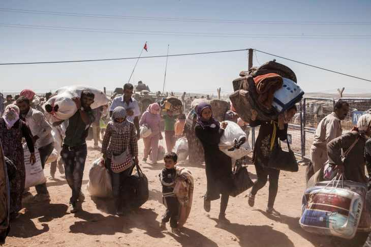 Syrian Kurdish refugees cross into Turkey from Syria near the town of Kobani.